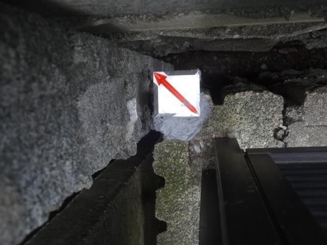 ブロック塀に貼り付けられた斜め矢印の金属標