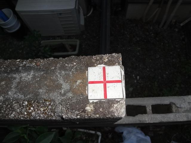 ブロック塀に貼り付けられた十字の金属標